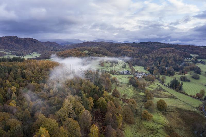 Stunning aerial drone landscape image from in the clouds looking down on hills and valleys on a vibrant Autumn Fall morning stock photo