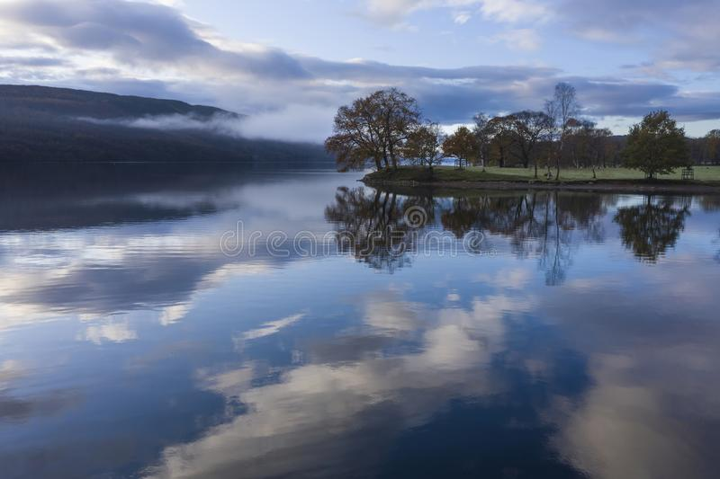 Breathtaking vibrant aerial drone landscape images over Coniston Water at sunrise on beautiful Autumn Fall morning stock photography