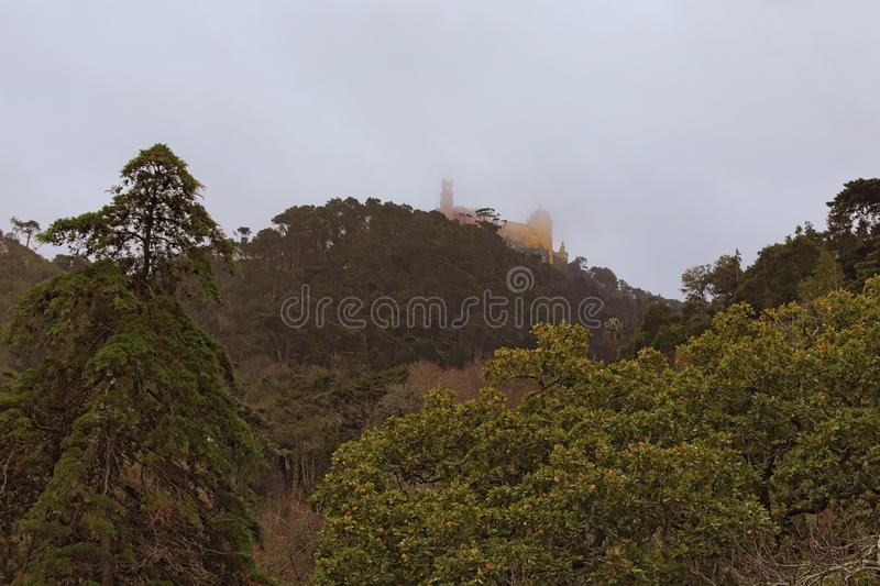 Stunning aerial view of The Pena National Palace in thick fog. Dramatic sky with thunderclouds. royalty free stock image