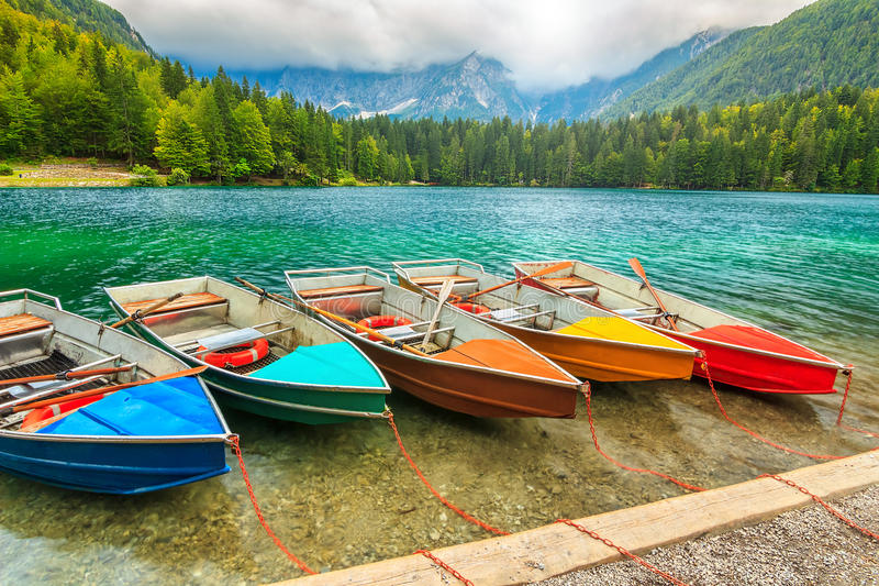 Stunning alpine landscape and colorful boats,Lake Fusine,Italy,Europe stock photo