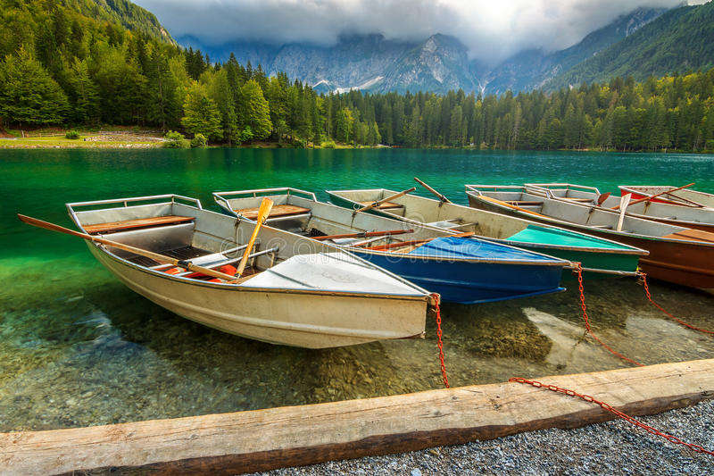 Stunning alpine landscape and colorful boats,Lake Fusine,Italy,Europe royalty free stock image
