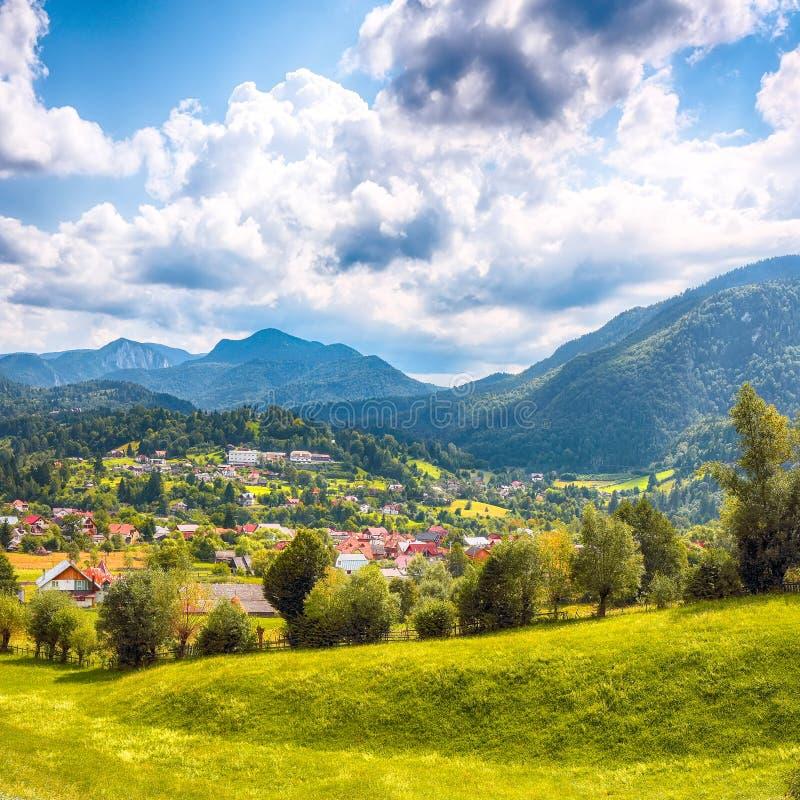 Stunning alpine landscape with green fields and Piatra Craiului mountains in Dambovicioara Commune. Location: Podu Dambovitei village, Arges County royalty free stock image