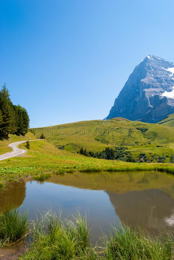 the stunning Alpine panorama of the Northern wall of the Eiger peak is reflected in a small mountain lake. Grindelwald Bernese Alp stock images