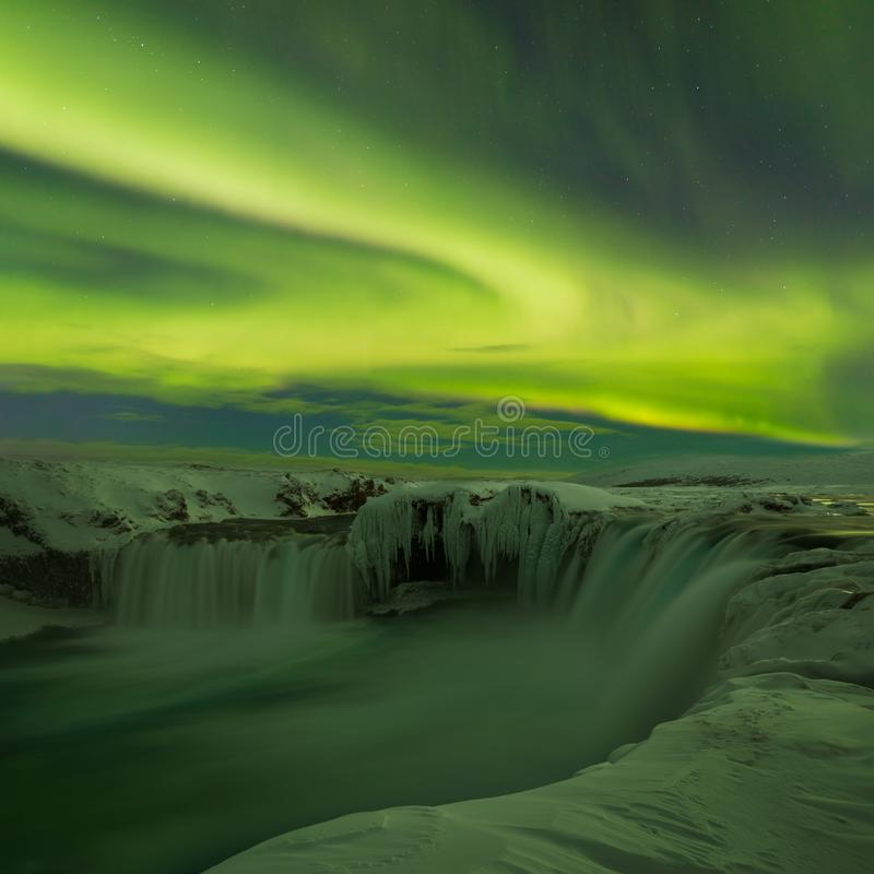 A stunning aurora above the landscape of Godafoss waterfall in winter Iceland. Green northern lights. Starry sky with polar lights stock image