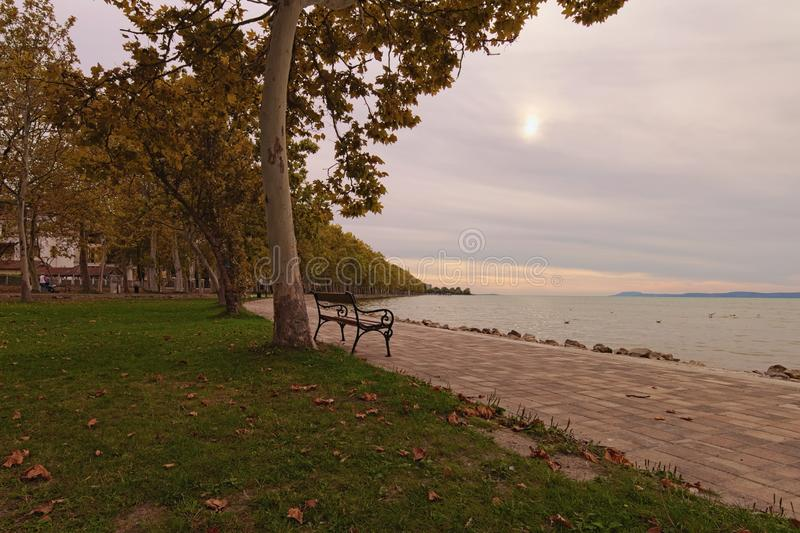 Stunning autumn landscape view of beautiful Lake Balaton during sunset. Plane trees alley is famous touristic place royalty free stock image
