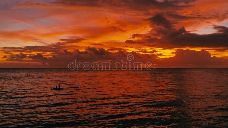 Stunning beautiful aerial drone image of a red tropical sunset above the sea ocean with two man in a canoe fishing stock images
