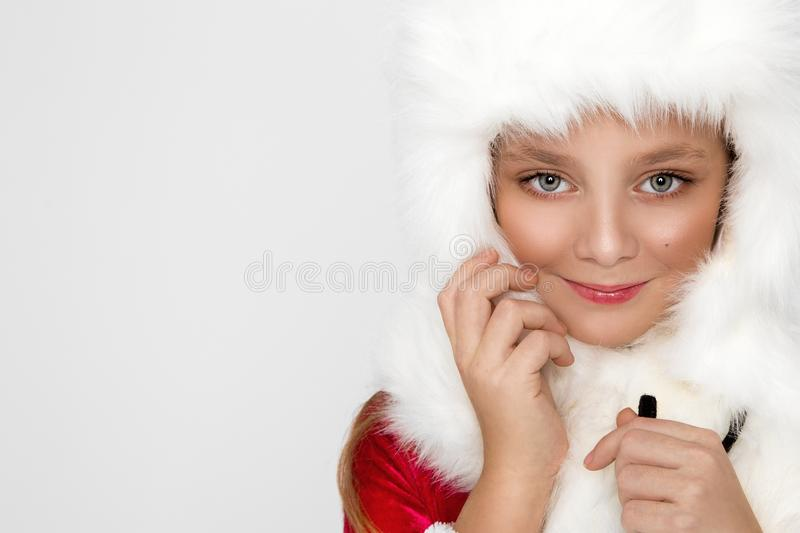 Stunning beautiful little girl with long blond hair , He has on his head a white cap with fur,. Joyfully look into the lens at Christmas time royalty free stock photo
