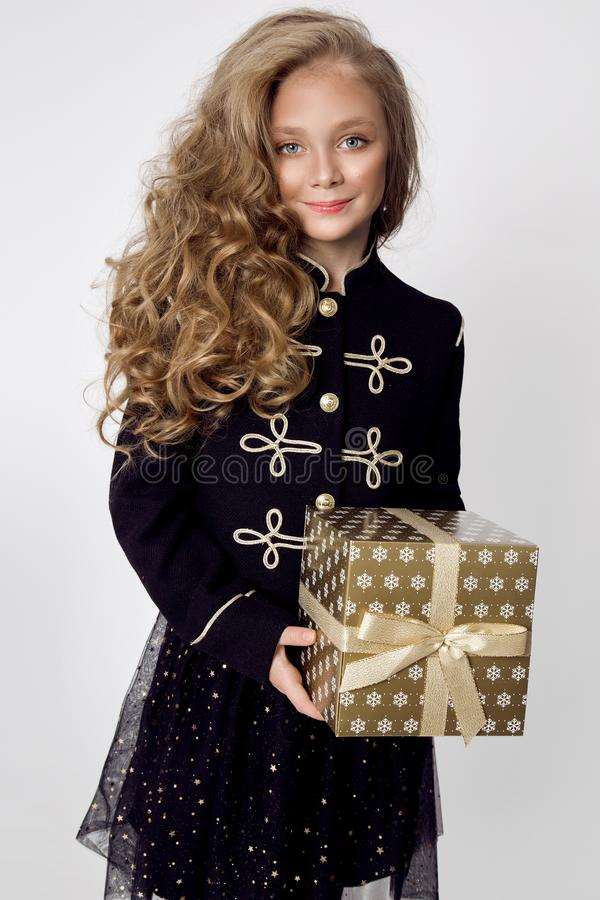 Stunning beautiful little girl with long blond hair holds in her hands gifts. Joyfully look into the lens at Christmas time stock images