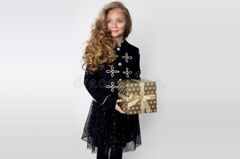 Stunning beautiful little girl with long blond hair holds in her hands gifts. Joyfully look into the lens at Christmas time royalty free stock photos