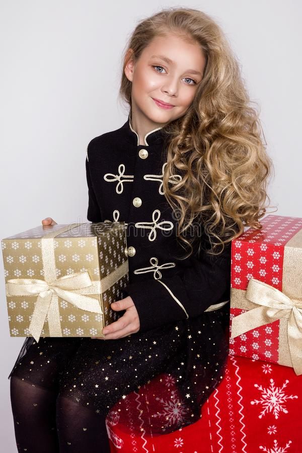 Stunning beautiful little girl with long blond hair holds in her hands gifts,. Joyfully look into the lens at Christmas time royalty free stock image