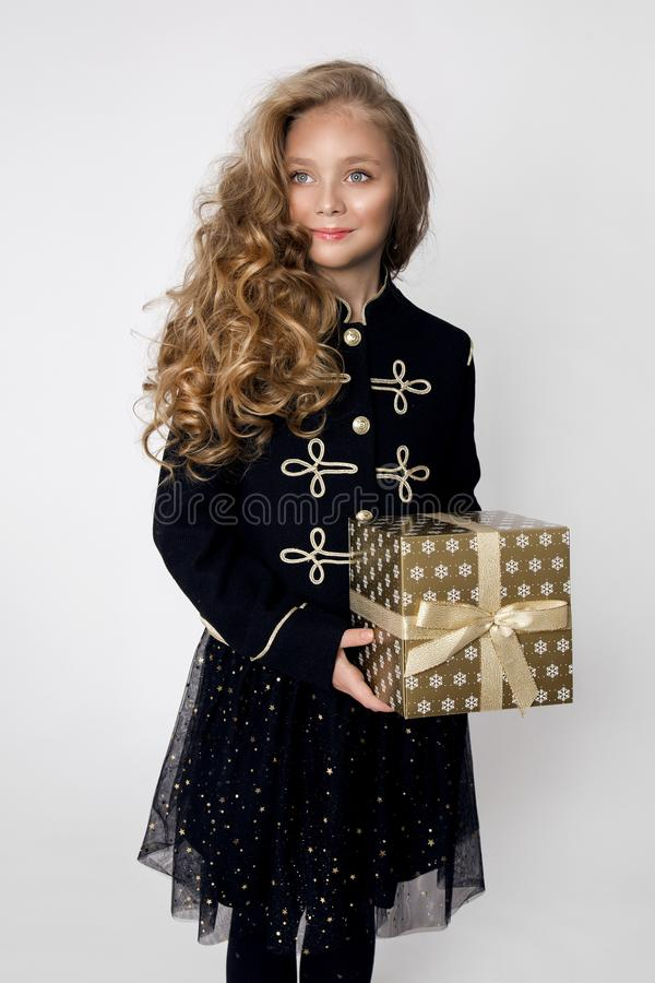 Stunning beautiful little girl with long blond hair holds in her hands gifts. Joyfully look into the lens at Christmas time royalty free stock image