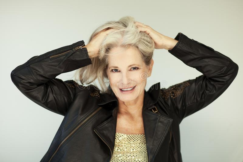 Stunning beautiful and self confident best aged woman with grey hair smiling into camera. Portrait with white background stock image