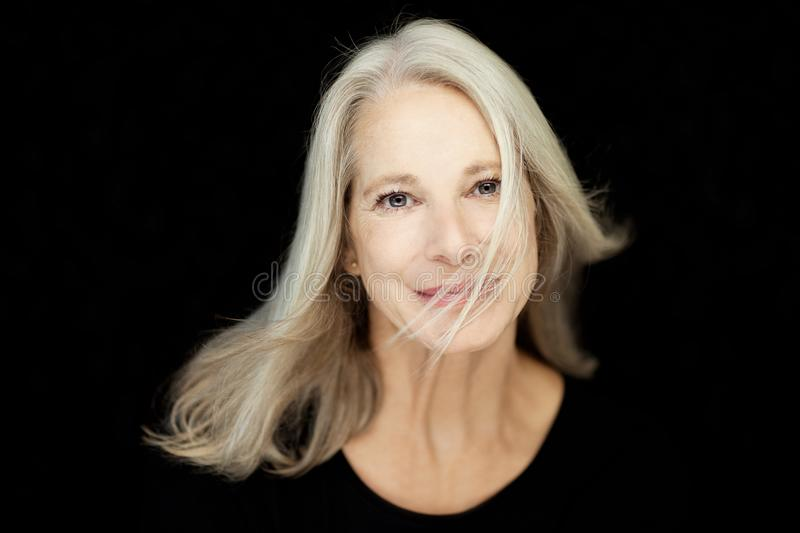 Stunning beautiful and self confident best aged woman with grey hair. Smiling into camera, portrait with black background royalty free stock photos