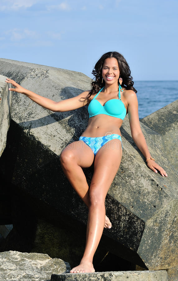 Stunning biracial woman at beach against jetty stock photography
