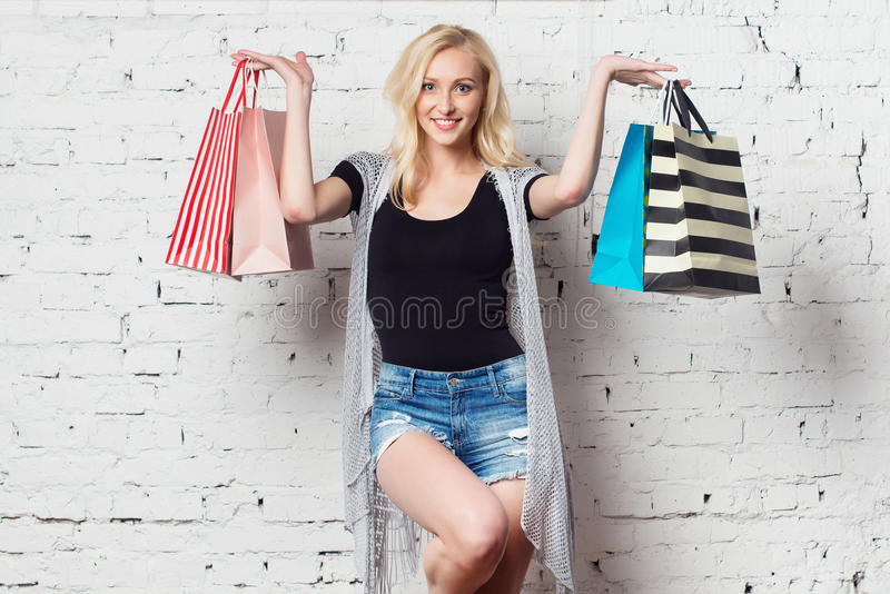 Stunning blond girl against the wall presenting royalty free stock photography