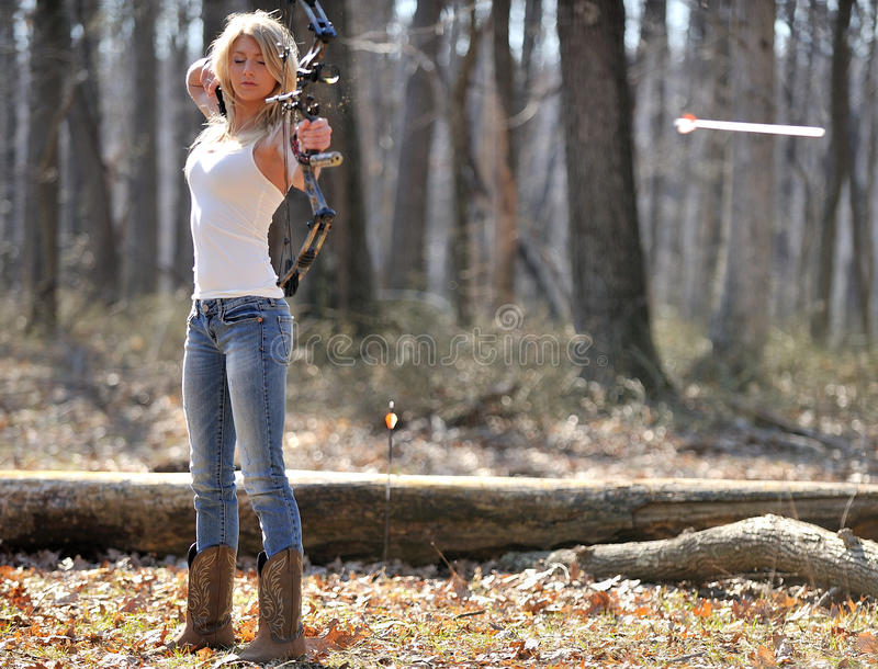 Stunning blonde female archer - arrow leaving bow. Stunning young blonde woman in white tank top and jeans shooting a compound bow - archery - arrow shown stock images