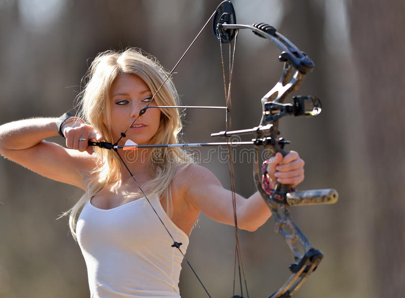 Stunning blonde female archer. Stunning young blonde woman in white tank top and jeans preparing to shoot a compound bow - archery - aiming stock photo