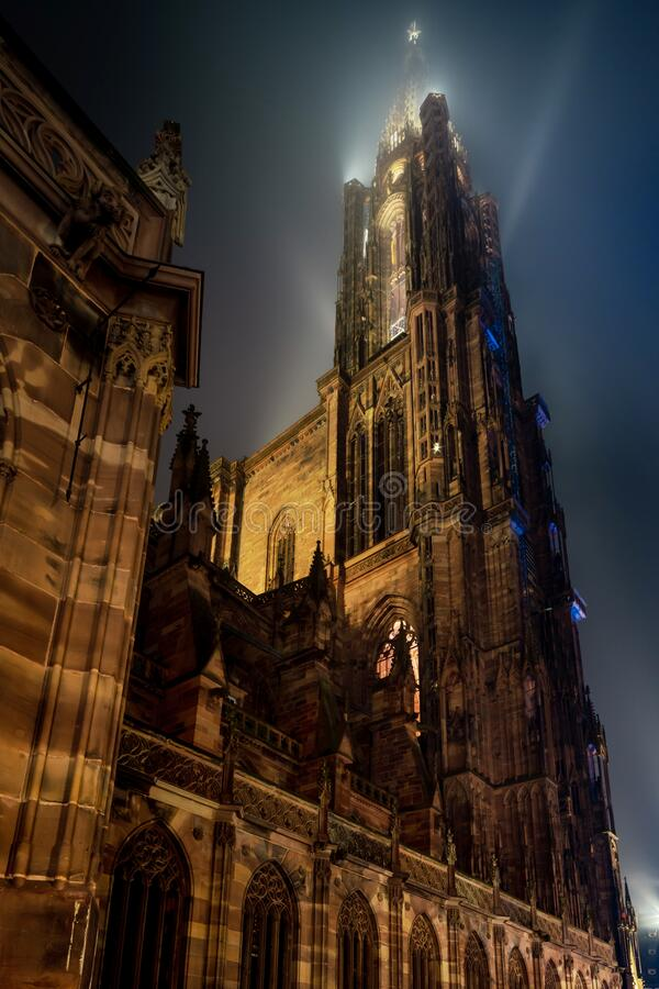 Stunning bottom view of Strasbourg Cathedral illuminated at night, Europe`s tallest building. The spire of the cathedral is lost in the sky and in the fog stock photos