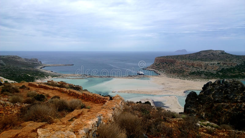 Stunning bright views of the famous Bay of Balos in Crete. Destroyed bright brown wall in foreground, the sea and the ship in the stock photo