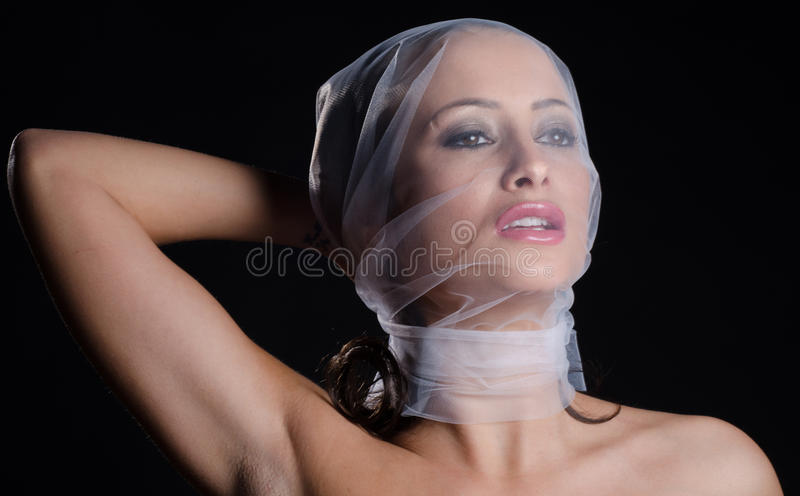 Stunning bruneete wearing a veil. Stunning brunette pulling a veil around her face royalty free stock images