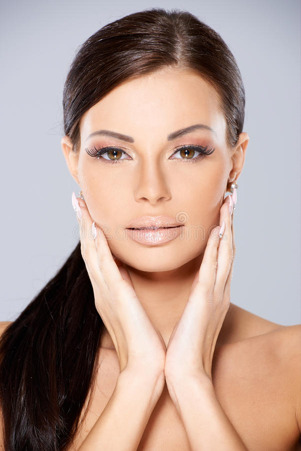 Stunning brunette with her hands to cheeks royalty free stock photo