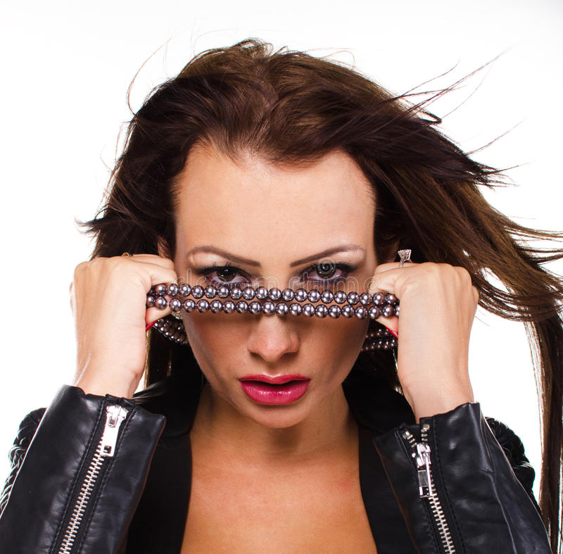 Stunning brunette rock chick wearing a black leath. Er jacket, holding a pearl necklace in front of her eyes stock image