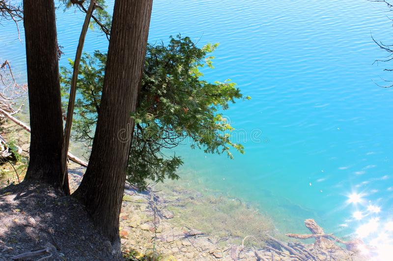 Stunning color of blue-green water in lake where glaciers melted but frigid water did not mix with warmer water below. Bright sunny day at the beach, with royalty free stock images