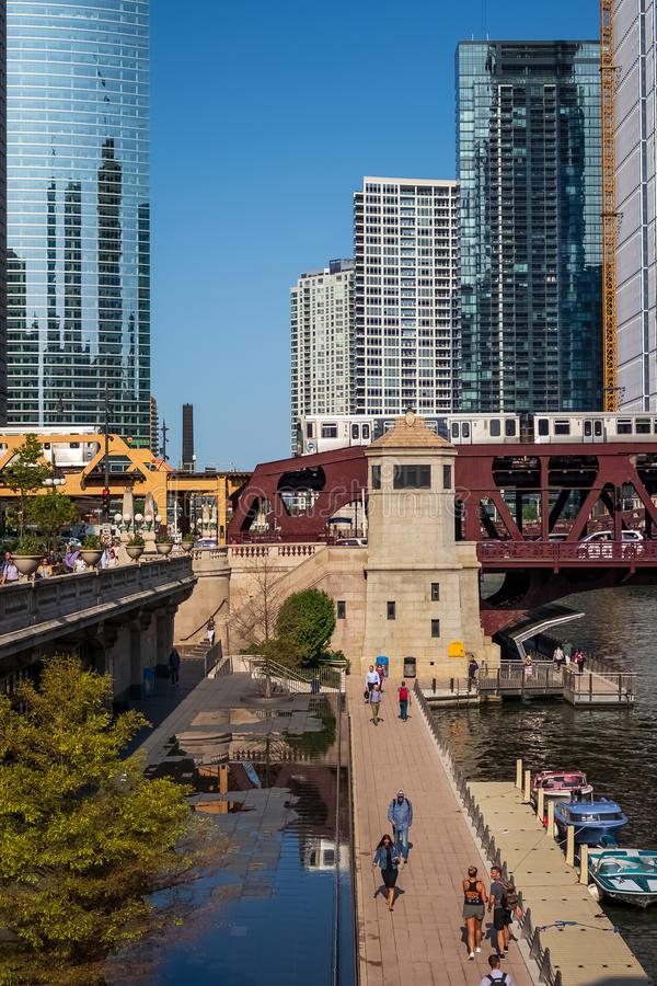 Stunning and colorful view of two el trains crossing the Chicago River and Wacker Dr. while commuters walk on riverwalk next to stock images