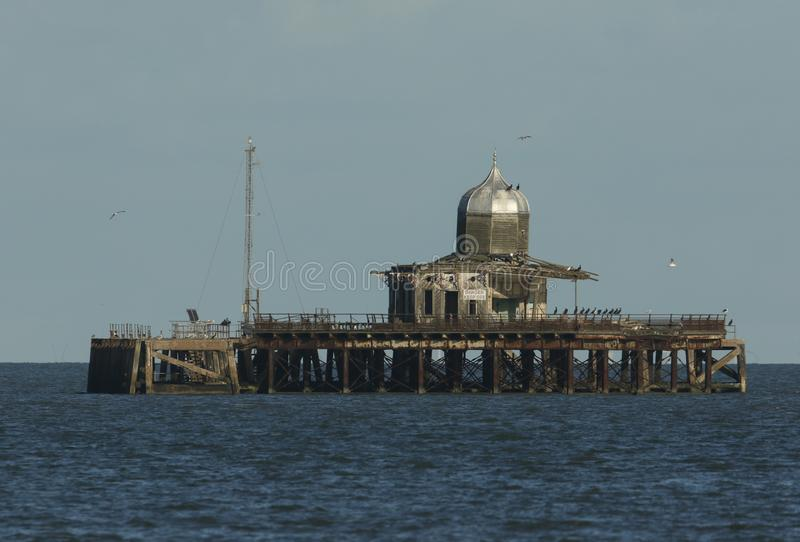 A derelict pier lying abandoned off the Kent coast of Herne bay England. It is being used by seabirds as a safe place to roost. royalty free stock images