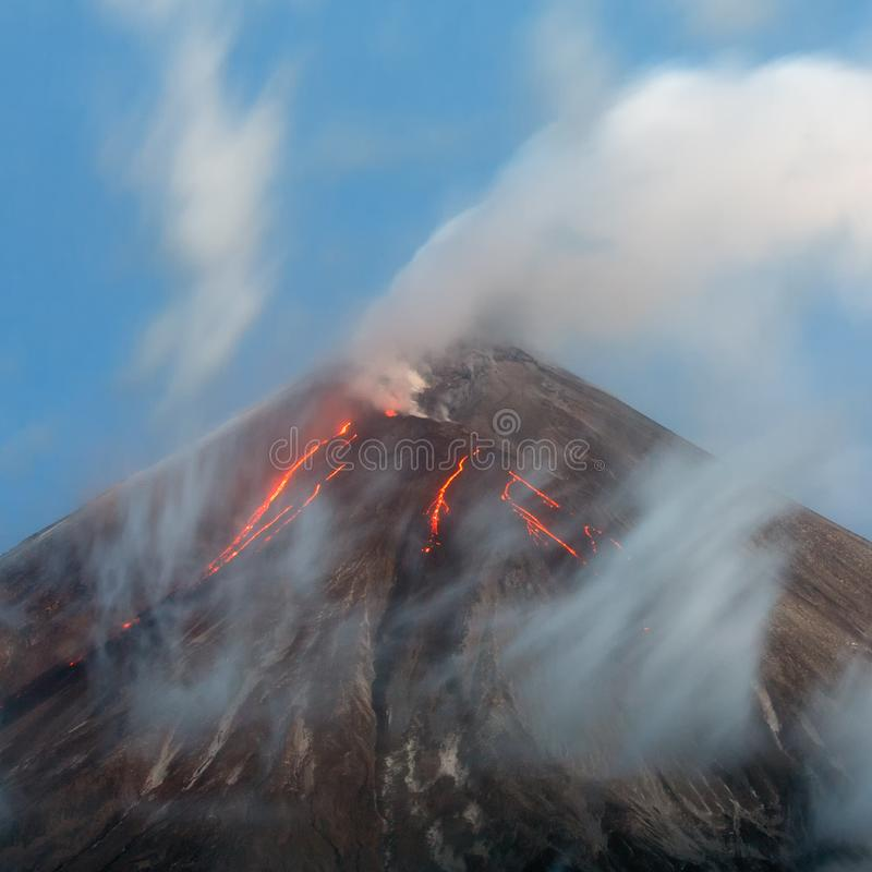 Stunning eruption volcanic landscape - red hot lava flows on slope of active volcano. Stunning volcanic landscape of Kamchatka Peninsula. View of top eruption royalty free stock photos