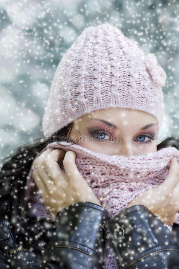 Stunning eyes. Cute girl with stunning eyes covering her face from a cold winter with pink scarf royalty free stock images
