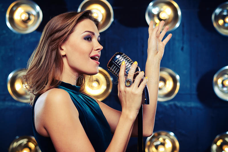 Stunning female vocalist singing with feelings and raising hand stock images
