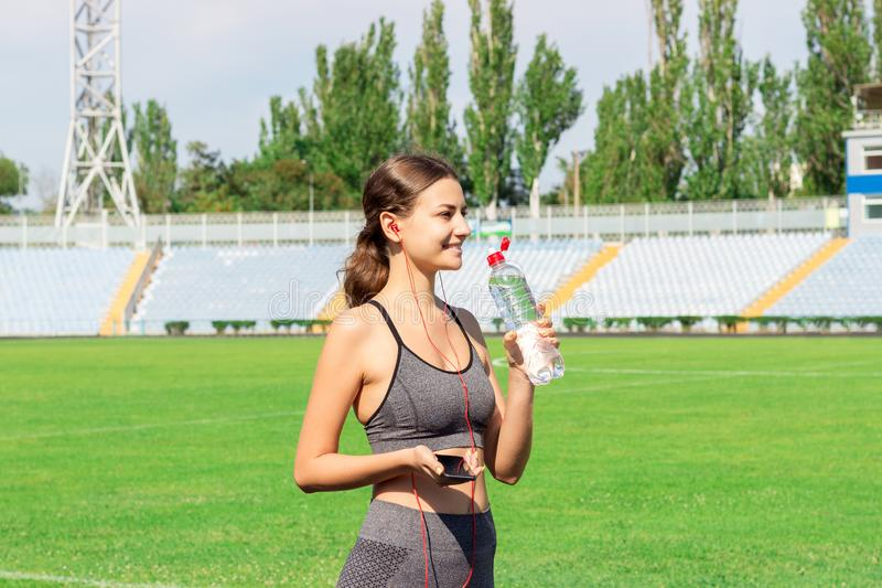 Stunning fitness woman drinking water and listening music after running at the stadium in sunny morning. Sports and healthy. Concept royalty free stock images