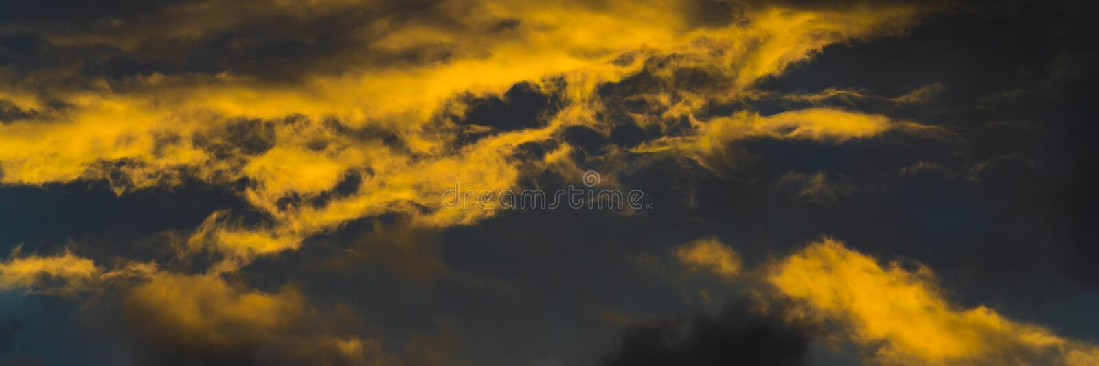 Stunning fluffy thunderstorm clouds illuminated by disappearing rays at sunset and dark thunderclouds floating across royalty free stock image