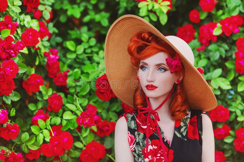Stunning girl with red lips in dress with a print of roses on a beautiful summer background. Young redhead model in hat on a backg stock image