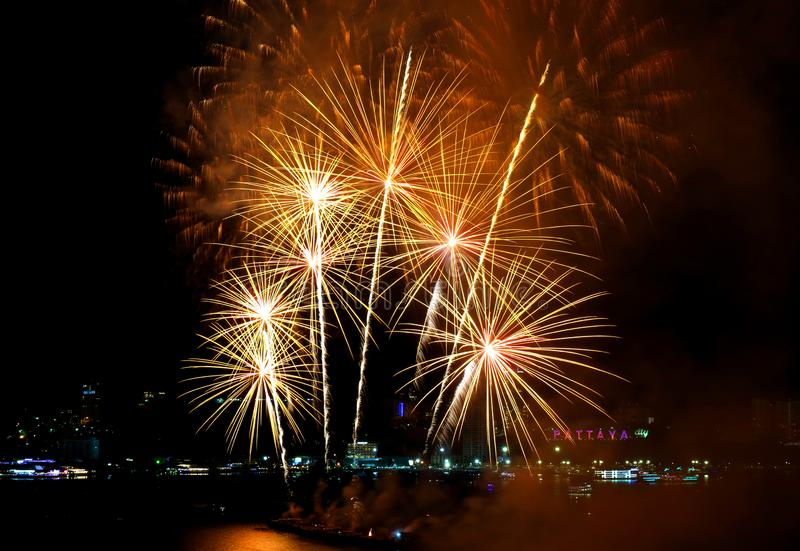 Stunning gold color fireworks exploding in to the night sky over Pattaya bay, Pattaya city, Thailand royalty free stock photo