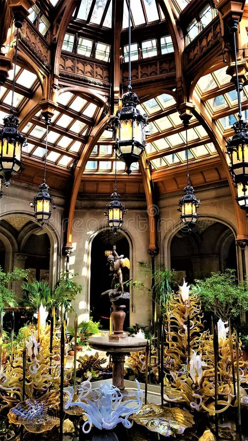 Chihuly in the Biltmore Estate. Stunning gold and white sculptures add elegance to the grandeur of the indoor winter garden atrium at the Biltmore Estate in stock photography