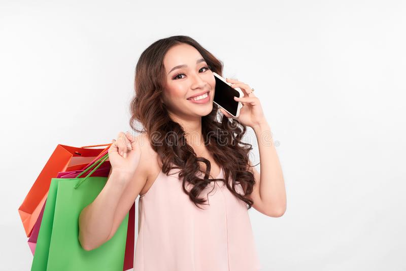 Stunning Happy girl with long hair standing with colorful shopping bags and talking on mobile phone, shopping stock photos
