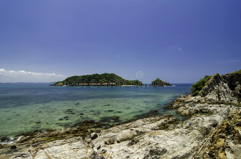 Stunning image rocky beach surrounded by clear blue sea water at Kapas Island, Malaysia. Island and blue sky background stock photo