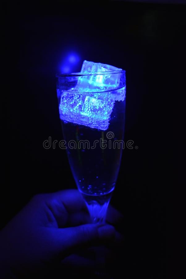 Stunning images of drinks with glowing ice cubes.  Bright colors with bubbles in a glass of champagne. Alcoholic and non-carbonated drinks in champagne bottles stock images