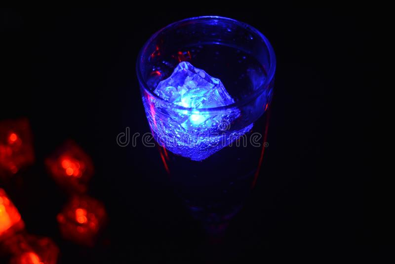 Stunning images of drinks with glowing ice cubes.  Bright colors with bubbles in a glass of champagne. Alcoholic and non-carbonated drinks in champagne bottles royalty free stock photography