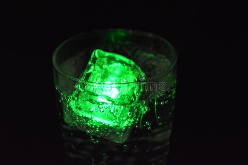Stunning images of drinks with glowing ice cubes.  Bright colors with bubbles in a glass of champagne. Alcoholic and non-carbonated drinks in champagne bottles royalty free stock image