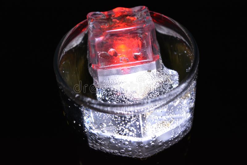 Stunning images of drinks with glowing ice cubes.  Bright colors with bubbles in a glass of champagne. Alcoholic and non-carbonated drinks in champagne bottles stock photography