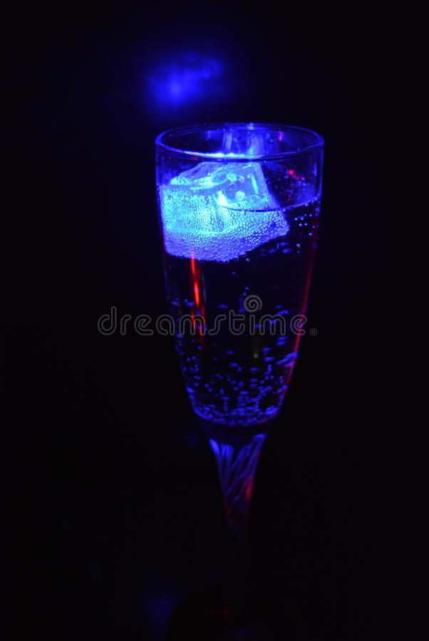 Stunning images of drinks with glowing ice cubes.  Bright colors with bubbles in a glass of champagne. Alcoholic and non-carbonated drinks in champagne bottles stock image