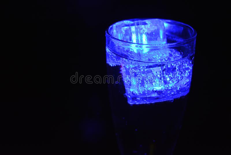 Stunning images of drinks with glowing ice cubes.  Bright colors with bubbles in a glass of champagne. Alcoholic and non-carbonated drinks in champagne bottles stock photo