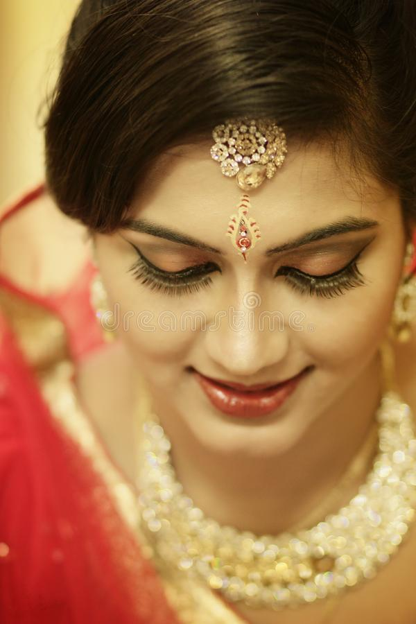 Stunning Indian bride dressed in Hindu red traditional wedding clothes sari embroidered with gold jewelry and a veil smiles tender royalty free stock photos
