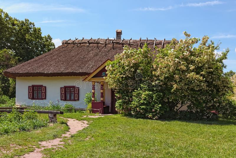 Stunning landscape of ancient clay house with flower bed in sunny spring day. Pereyaslav-Khmelnitsky Museum of Folk Architecture. And Life of the Middle stock photography