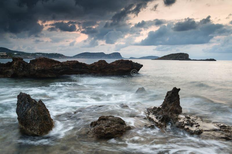 Stunning landscape dawn sunrise with rocky coastline and long ex stock image