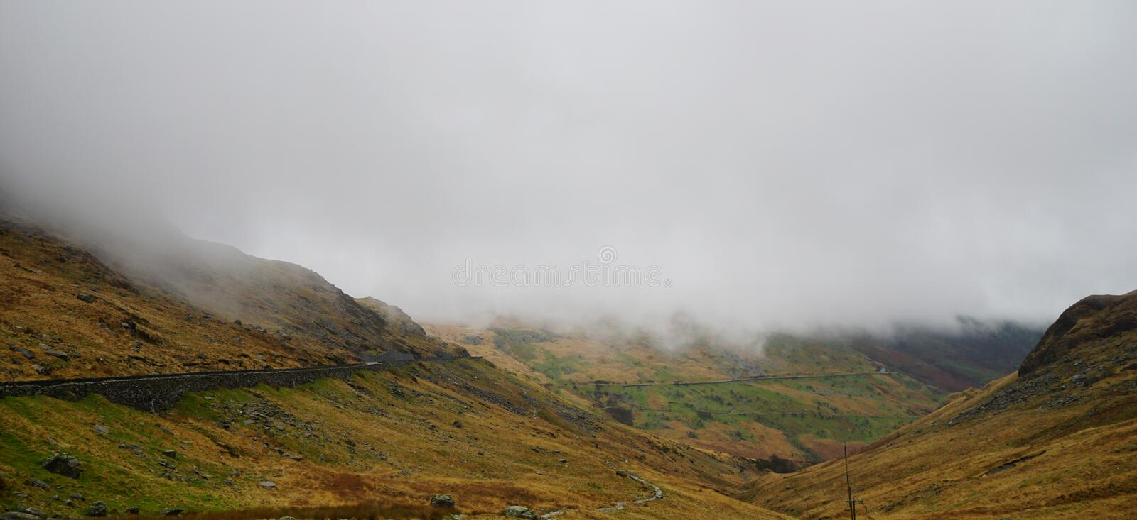 Stunning Mountains in Snowdon, Wales, United Kingdom. Stunning landscape with foggy and moody skies among the mountains, covered with beautiful snow – royalty free stock image