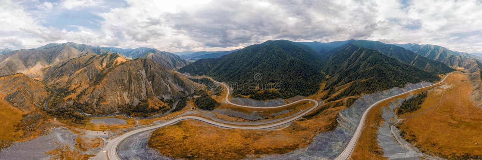 Stunning landscape of high mountains. Highway, coniferous forest on an autumn day. Photographing mountains with a quadrocopter stock images